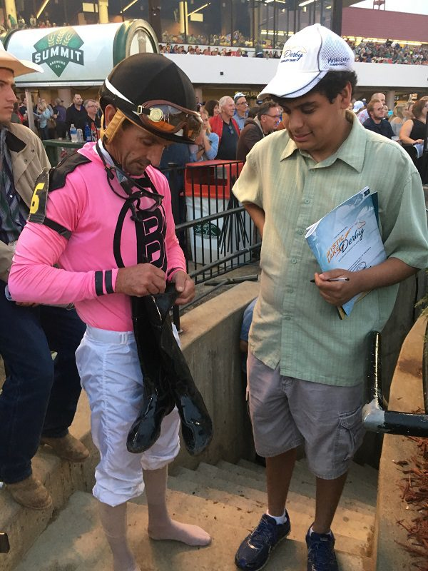 Albarado signs his riding boots for a young fan.